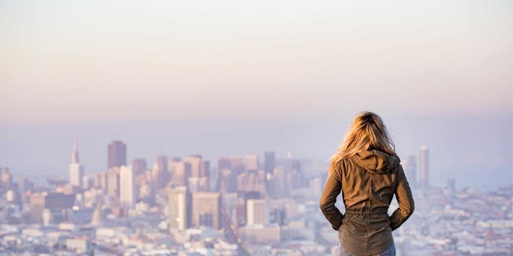 woman overlooking smoggy city hoping for a carbon tax