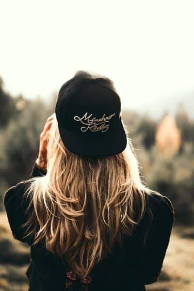 Woman wearing circular fashion baseball cap looking at nature