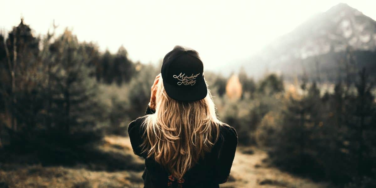 Woman wearing circular fashion baseball cap looking at nature