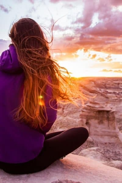 woman overlooking sunset wearing circular fashion