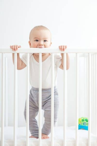 crib mattress naturepedic with baby holding onto crib rails