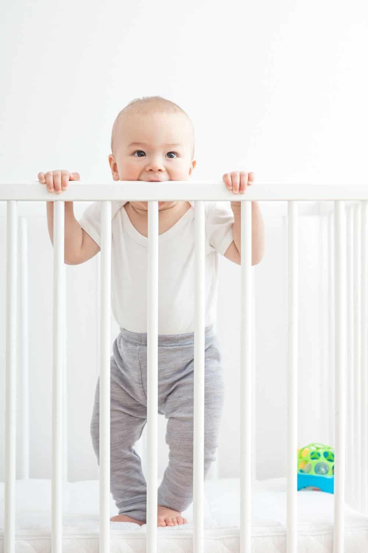crib mattress naturepedic with baby holding onto crib rails