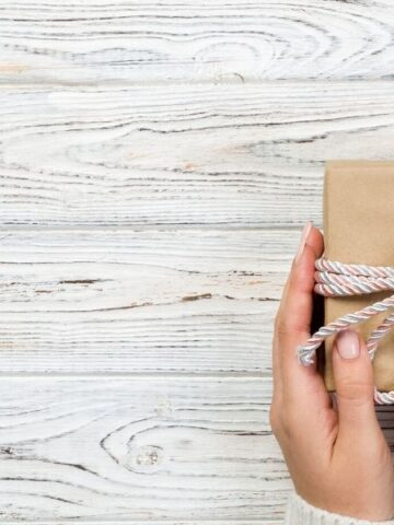 Woman's hand holding eco-friendly gift in recycled wrapping paper