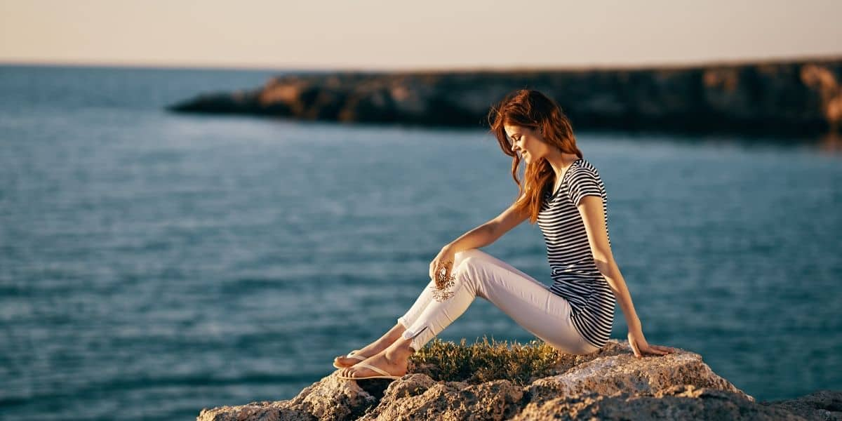 woman sitting by beach thinking about circular fashion