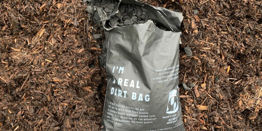 Bag of biochar on top of soil and compost mixture.