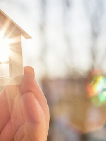hand holding small house with sun shining through window