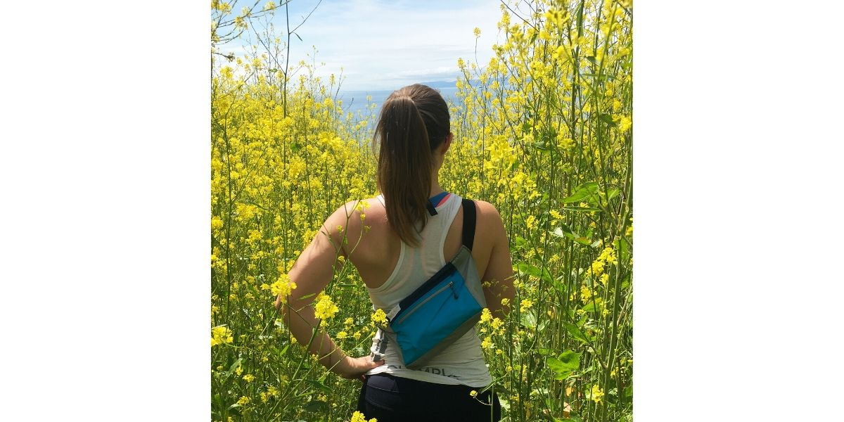 Woman wearing upcycled hip bag overlooking field of yellow flowers.
