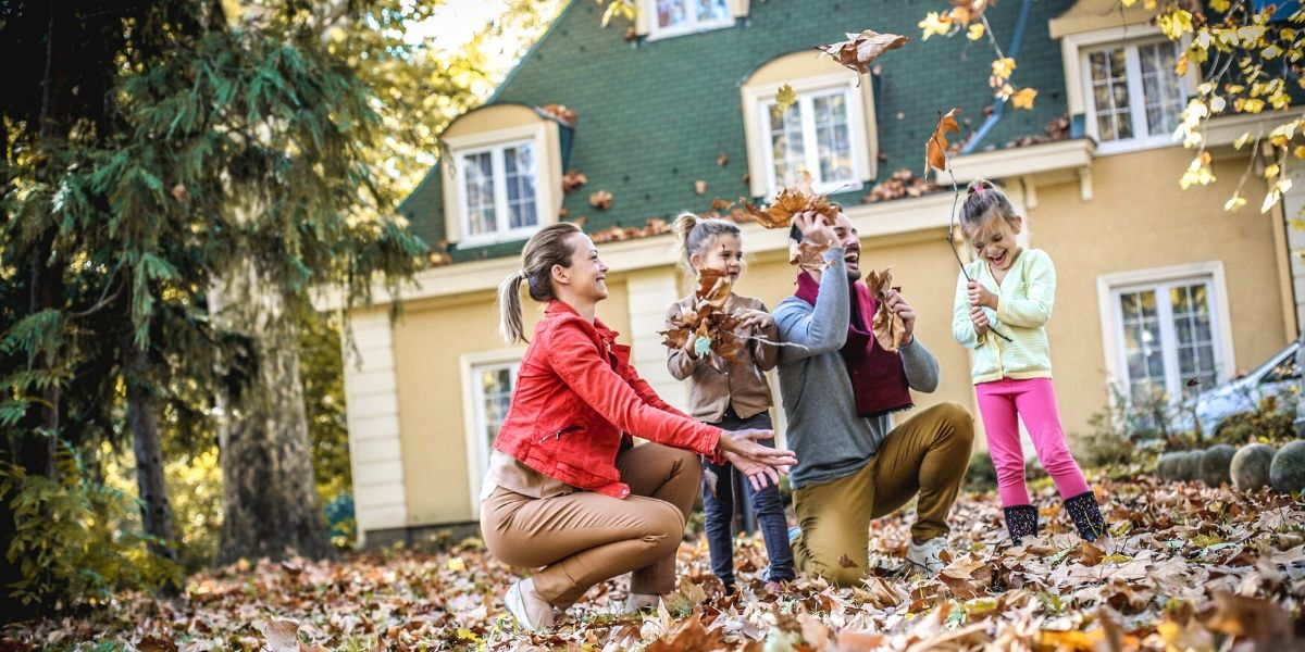 happy family throwing leaves outside of a sustainable home