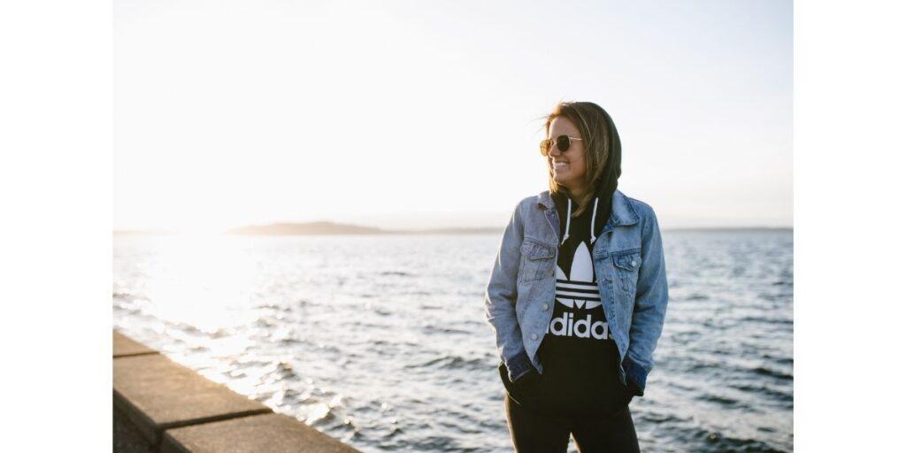 Soccer star Lauren Barnes wearing adidas sweatshirt by the ocean