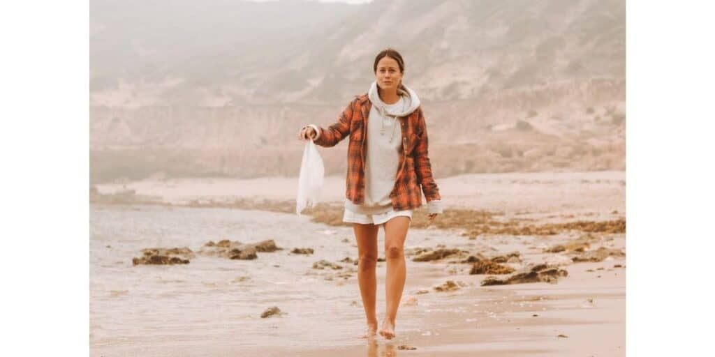 Soccer star Lauren Barnes by the ocean cleaning plastic waste