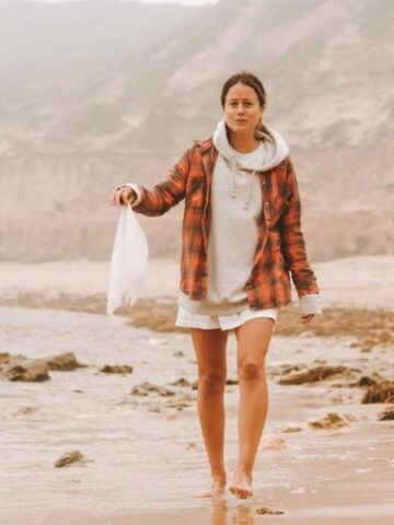 Soccer star Lauren Barnes by the ocean cleaning plastic waste