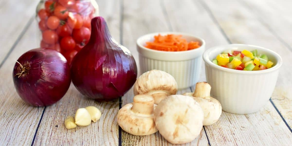 Onions, mushrooms and chopped veggies on wood table.