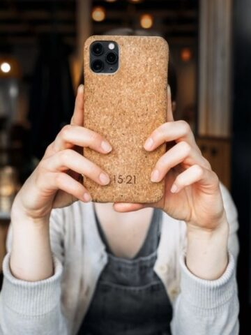 Hands holding phone case made from cork bark