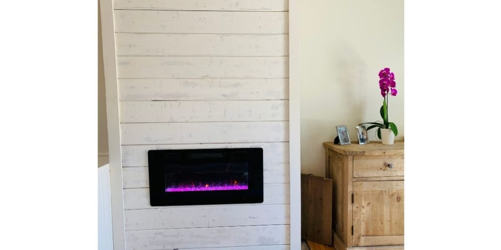 Electric fireplace insert surrounded by upcycled shiplap boards.